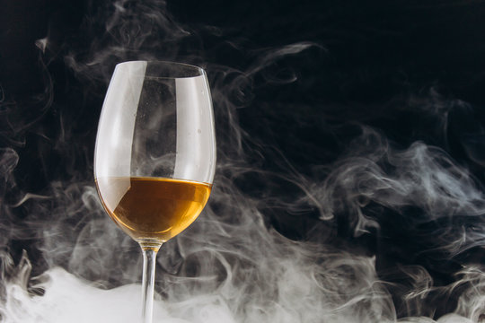 a glass of white wine on a black background. the smoke from the hookah envelops the glass. rest, holiday. alcoholic drink closeup. white fog
