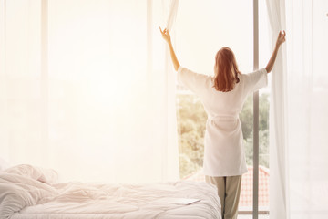 view back woman opening curtains in a white bedroom Wall mural