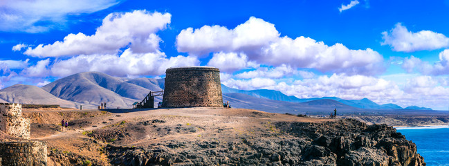Wall Mural - landscapes of volcanic Fuerteventura - view with Toston tower in El Cotillo. Canary islands