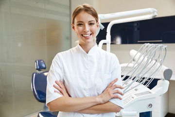 Beautiful happy young woman doctor in medical dentist center.