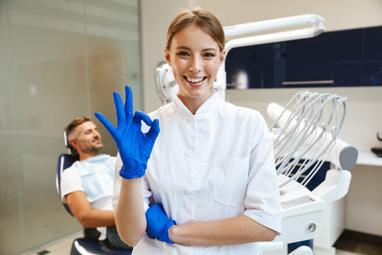 Beautiful happy young woman doctor in medical dentist center showing okay gesture.