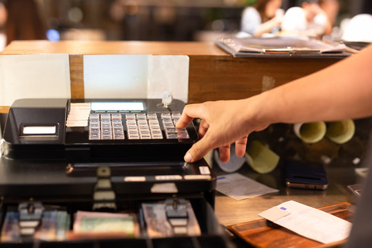 Shot in low light hand pressing electronic cash register in a shop.