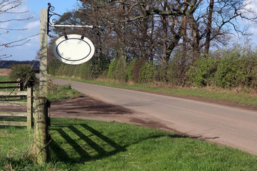 Blank hanging name sign, next to a rural country road.