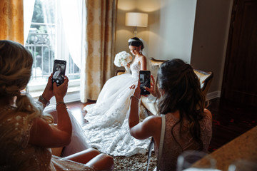 brides friends take photos with the bride