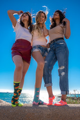 3 young woman posing at the beach