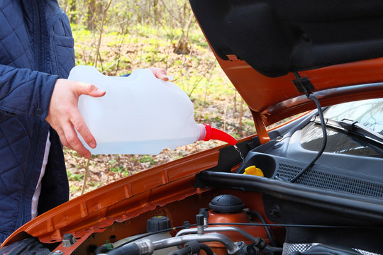 Car maintenance concept. Filling windshield washer fluid on car. Driver with washer fluid in his hands, close up.