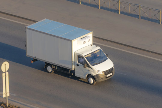 Several delivery van and white logistic truck driving on the highway.