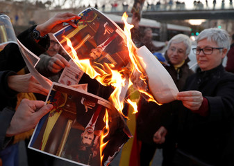 Pro-independence Catalan protesters burn pictures of Spain's King Felipe during a protest in Barcelona