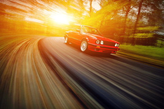 Classic red cabrio sport car driving fast on the open road