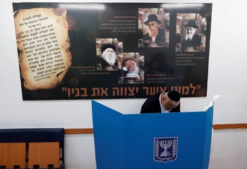 An ultra-Orthodox Jewish stands behind a voting booth as Israelis vote in a parliamentary election, at a polling station in Jerusalem