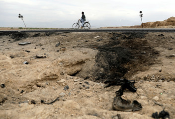 An Afghan man rides on a bicycle past the site of a car bomb attack where U.S soldiers were killed near Bagram air base, Afghanistan
