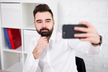 portrait of handsome man taking selfie photo with smartphone