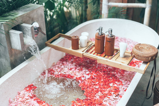 Cosmetic products on bath tub with flowers