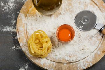 Italian raw homemade pasta tagliatelle at concrete table