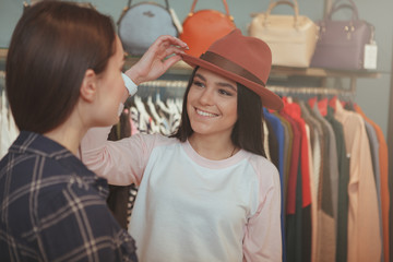 Beautiful cheerful young woman trying on a hat at clothing store, talking to her friend, copy space. Two young women enjoying shopping for clothing and accessories together