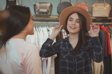 Charming young woman trying on a hat at clothing store, smiling at her friend, asking for opinion. Female friends shopping at clothing boutique together. Consumerism, fashion, sales concept