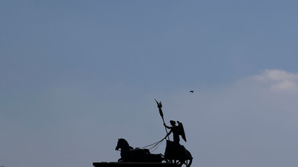 A bird flies beside the silhouette of the Quadriga on top of the Brandenburger Gate in Berlin