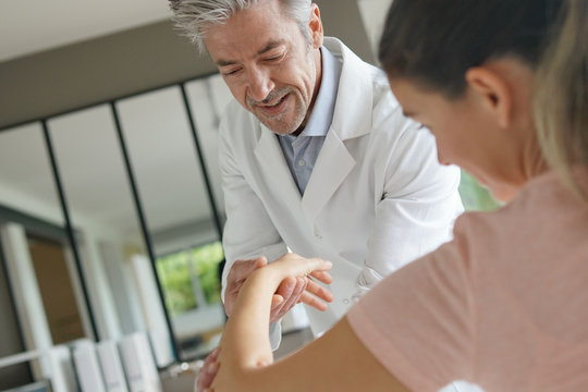 Physiotherapist working with patient's wrist injury