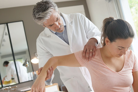 Physiotherapist helping patient with shoulder injury