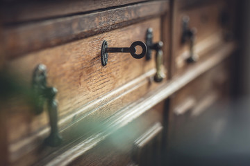 Fototapeta Vintage. Old chest of drawers with a key in the keyhole. Shallow DOF obraz