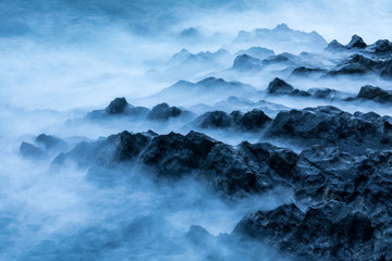 Waves crashing on the rocky shore and creating dreamy mist on the beach in Seychelles