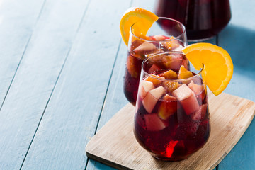 Red wine sangria in glass on blue wooden table. Copyspace