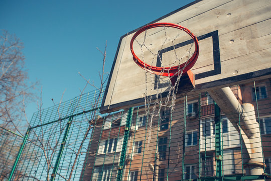 Basketball hoop with backboard in residential district for street basketball game, outdoors sports and recreation, urban environment, retro toned image