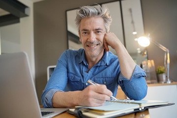 Mature man working from home smiling at camera