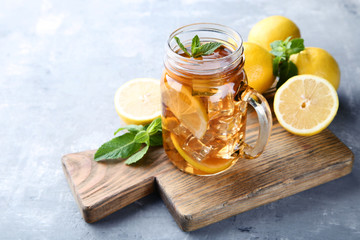 Wall Mural - Ice tea in glass jar with lemon and mint leafs on wooden table
