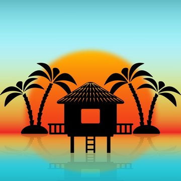 Silhouettes of bungalow and palm trees against rising sun