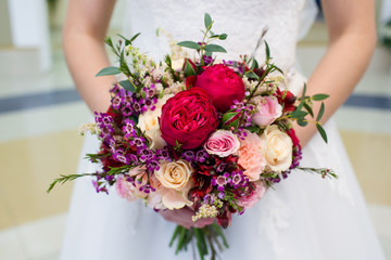 Beautiful  wedding bouquet of flowers in the hands of the bride Fototapete