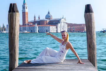Autocollant pour porte Venise Happy beautiful girl against the background of turquoise water at the Grand Canal next St Marks Square in Venice, Italy.Concept of traveling and vacation in summer Venice.