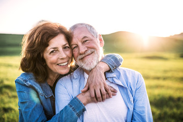Senior couple outside in spring nature at sunset.