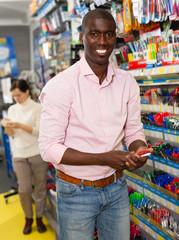 Smiling African man choosing pens and pencils