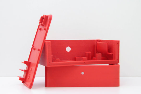 3d printing red plastic case isolated on white background, produced from pla, horizontal view, macro