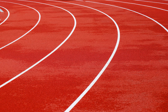 Red artificial running track with white round dividing lines, treadmill rubber texture