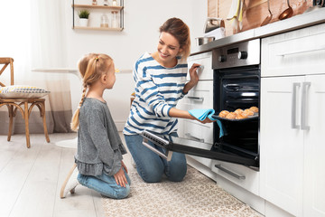 Mother and her daughter taking out cookies from oven in kitchen