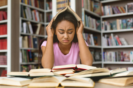 Stressed black girl student preparing for examination in library