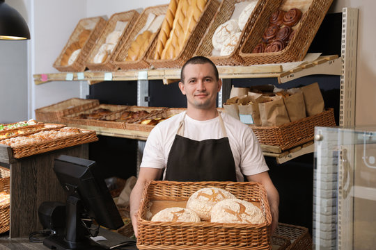 Portrait of professional baker holding tray with fresh bread near showcase in store