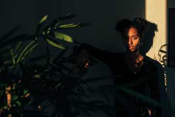 Woman standing near plant with shadow light Fotoväggar