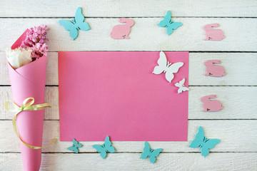 Obraz Różowo-białe tło z pudełkiem przewiązanym wstążką, kwiatami i zajączkami - fototapety do salonu