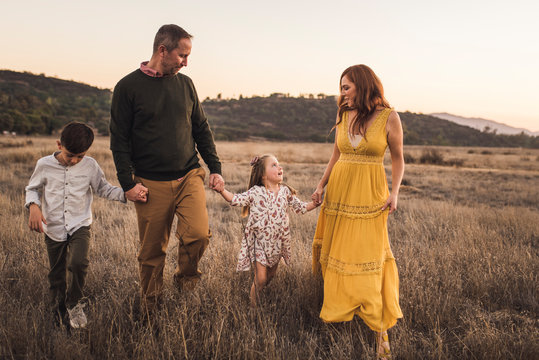 Young family holding hands while walking in California field at sunset
