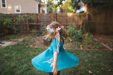 a little girl in a fairy flower headband spins and dances in her yard