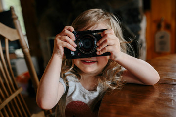 toddler girl learning how to take pictures with a camera