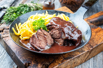 Traditionelle deutsche geschmorte Ochsenbacke in brauner Rotwein Sauce mit Spätzle als closeup in einer schmiedeeisernen Pfanne