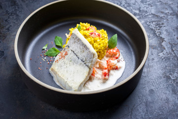 Fried haddock filet with saffron rice and shell prawns in crab sauce as closeup on a modern design bowl with copy space
