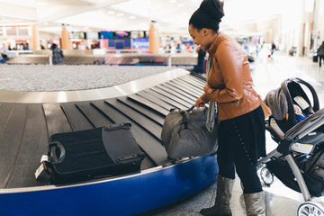 Woman picking up luggage from baggage carousel at airport