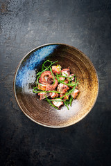 Traditional French octopus braised cooked with Salicornia, lemon curd and spice as top view in a modern design Japanese bowl with copy space