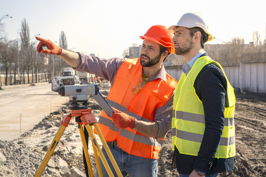 two male surveyor engineer with a device working on a construction site in a helmet