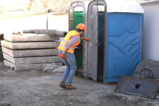worker engineer in helmet at a construction site runs to the restroom